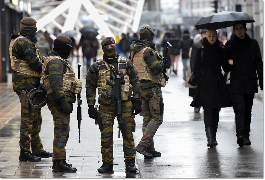 """Soldiers patrol the Rue Neuve pedestrian shopping street in Brussels on November 21, 2015. All metro train stations in Brussels will be closed on November 21, the city's public transport network said after Belgium raised the capital's terror alert to the highest level, warning of an """"imminent threat"""". As Europe tightens security a week on from the jihadist attacks in Paris that left 130 people dead, Belgium's OCAM national crisis centre raised its alert level to 4 early on November 21, """"signifying a very serious threat for the Brussels region"""". AFP PHOTO / JOHN THYS / AFP / JOHN THYS"""
