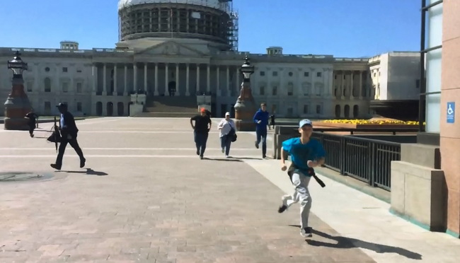 Tourists run for safety past the entrance to the U.S. Capitol Visitors Center (R) in this video frame grab from WRC-TV footage after a shooting in Washington March 28, 2016.  REUTERS/WRC-TV Via Reuters  NO SALES. NO ARCHIVES. FOR EDITORIAL USE ONLY. NOT FOR SALE FOR MARKETING OR ADVERTISING CAMPAIGNS. MANDATORY CREDIT.        TPX IMAGES OF THE DAY