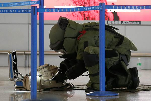 A bomb disposal expert checks a luggage near the site of a blast at a terminal in Shanghai's Pudong International Airport, China, June 12, 2016. REUTERS/Aly Song TPX IMAGES OF THE DAY