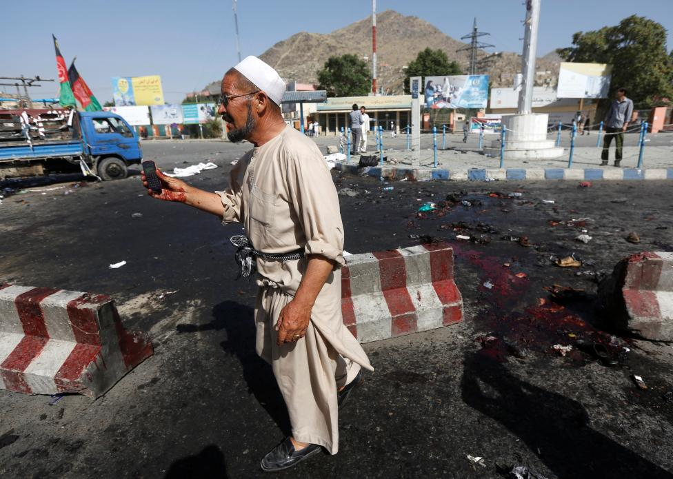 An Afghan man picks up a phone belonging to a victim after a suicide attack in Kabul, Afghanistan July 23, 2016. REUTERS/Omar Sobhani