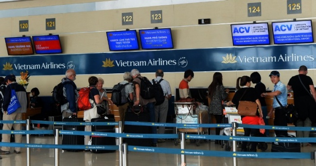 TO GO WITH Vietnam-economy-aviation-IPO,ANALYSIS BY CAT BARTON In this picture taken on November 11, 2014, passengers check-in for Vietnam Airlines flights at Noi Bai airport in Hanoi. After decades of speculation and multiple failed attempts, Vietnam Airlines' long-awaited IPO is set for take-off on November 14, but experts say it is unlikely to boost the communist country's lacklustre privatisation drive. AFP PHOTO / HOANG DINH NAM