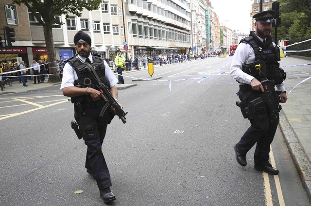 Armed police officers patrol at the scene of a knife attack in Russell Square in London, Britain August 4, 2016. REUTERS/Neil Hall